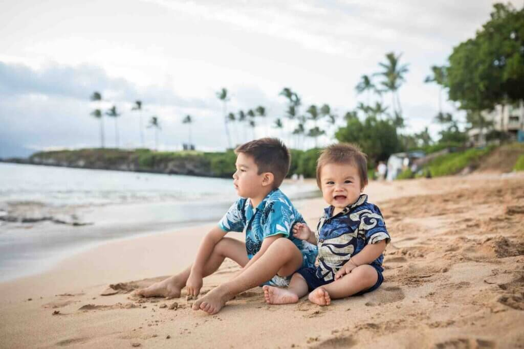 Get cute Maui family photos on your next trip to Hawaii with kids! Image of two young boys wearing Aloha shirts sitting barefoot on a Maui beach.