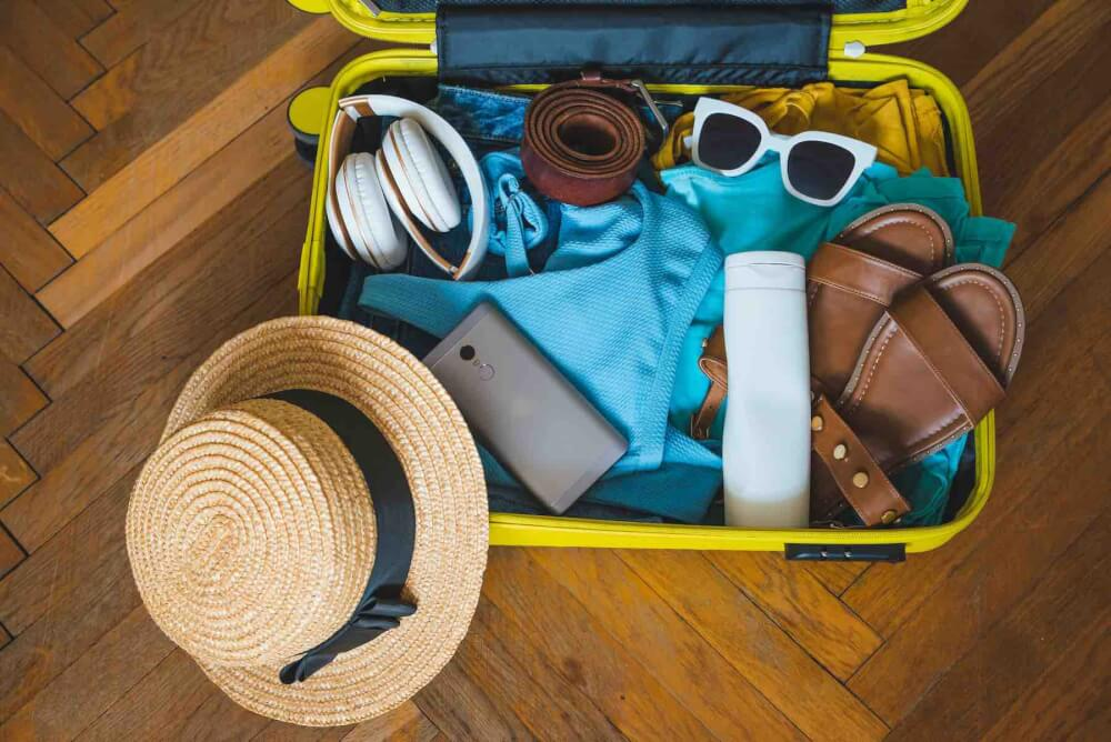 Find out what to add to your packing list for Maui by top Hawaii blog Hawaii Travel with Kids. Image of a yellow suitcase filled with items for a tropical vacation.