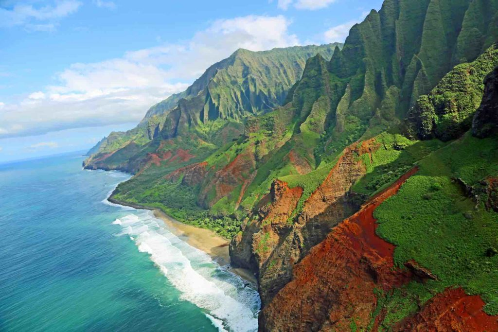 Exploring the Na Pali Coast is just one of the many best things to do on Kauai on a budget recommended by top Hawaii blog Hawaii Travel with Kids. Image of a rugged coastline.