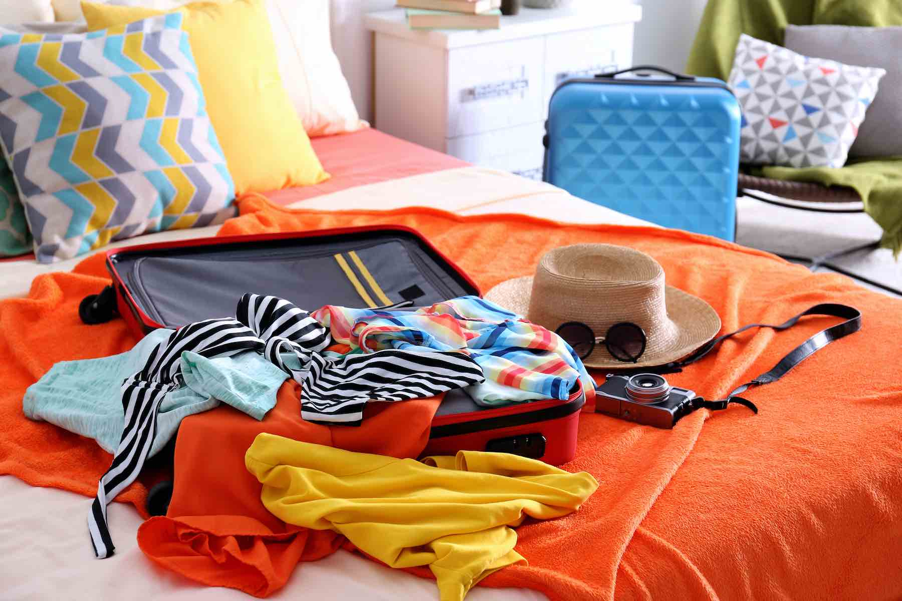 Find out the best Kauai packing list for families by top Hawaii blog Hawaii Travel with Kids. Image of Open suitcase with clothes and personal things packed for traveling