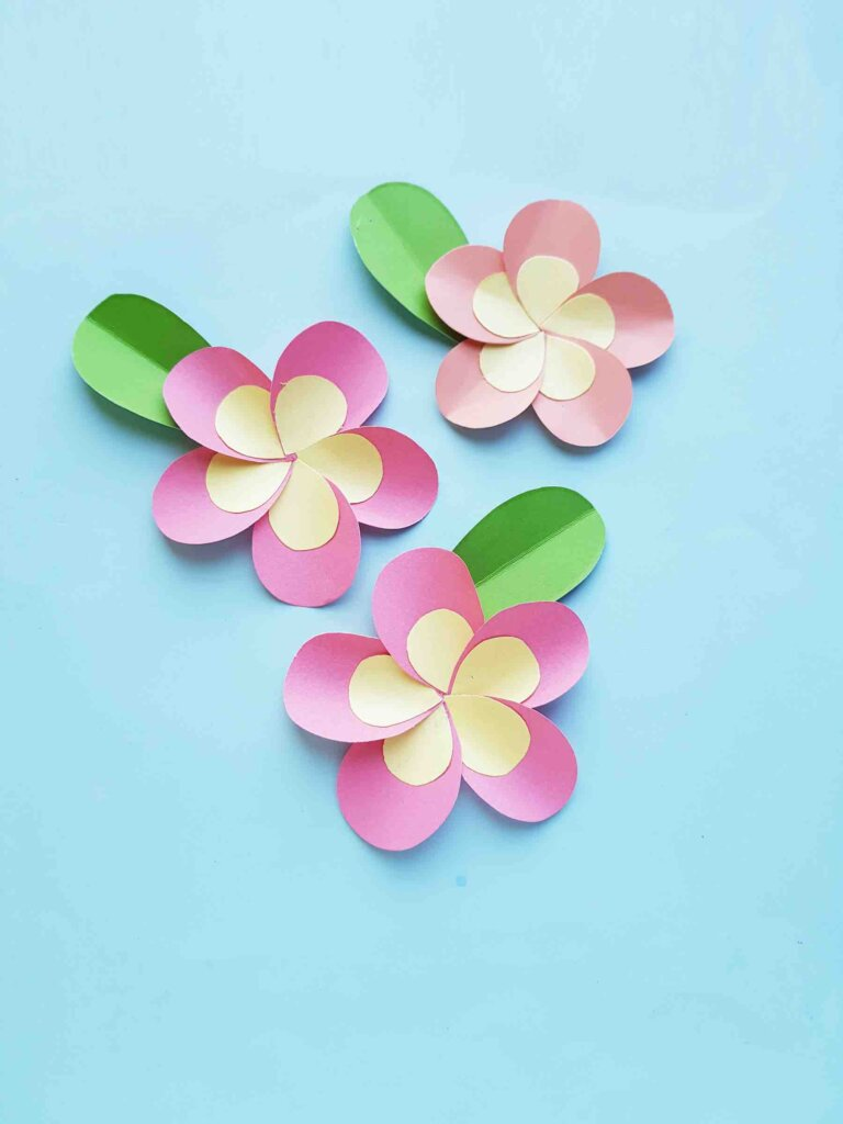 Get this paper flower tutorial by top Hawaii blog Hawaii Travel with Kids. Image of 3 paper plumeria flowers.