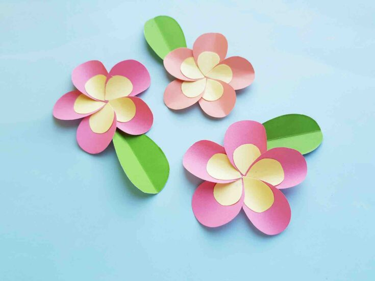 Learn how to make a plumeria paper flower craft by top Hawaii blog Hawaii Travel with Kids. Image of 3 pink plumeria flowers made out of paper.
