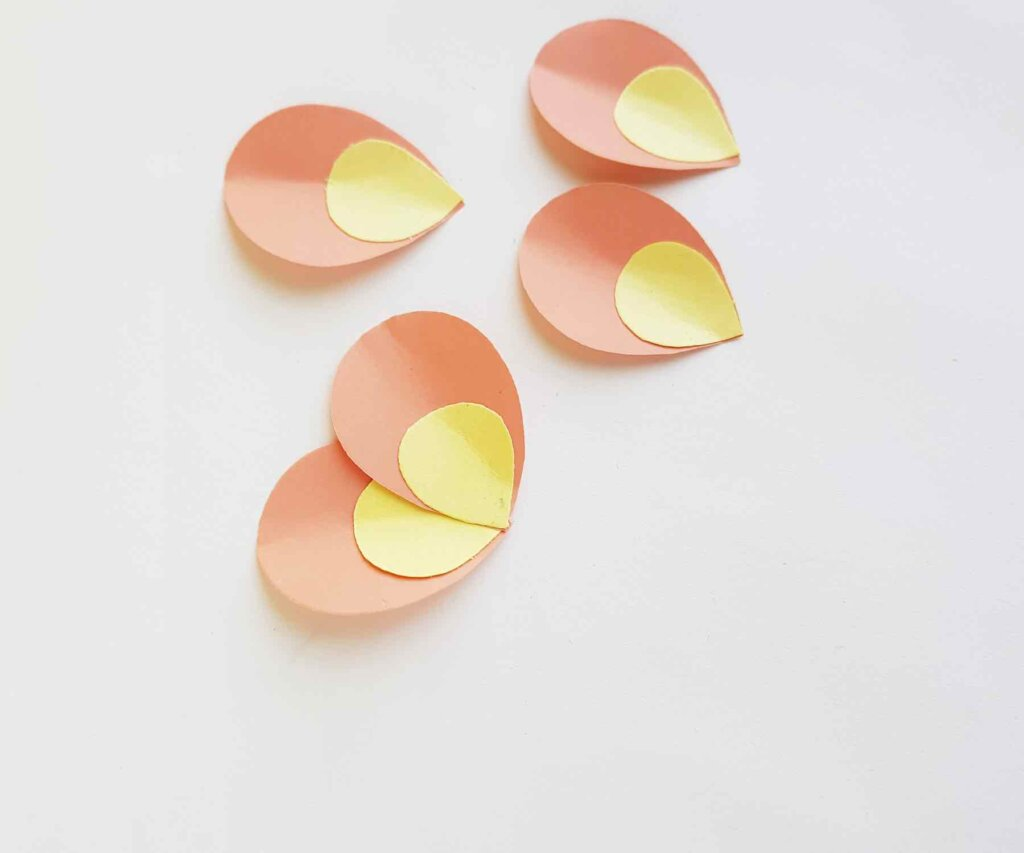 Layer the plumeria petals on top of each other to make paper flowers. Image of orange and yellow paper petals.