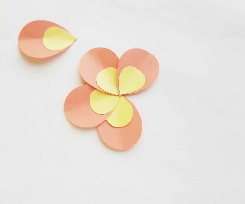 Keep layering petals to make a paper plumeria flower. Image of a paper flower.