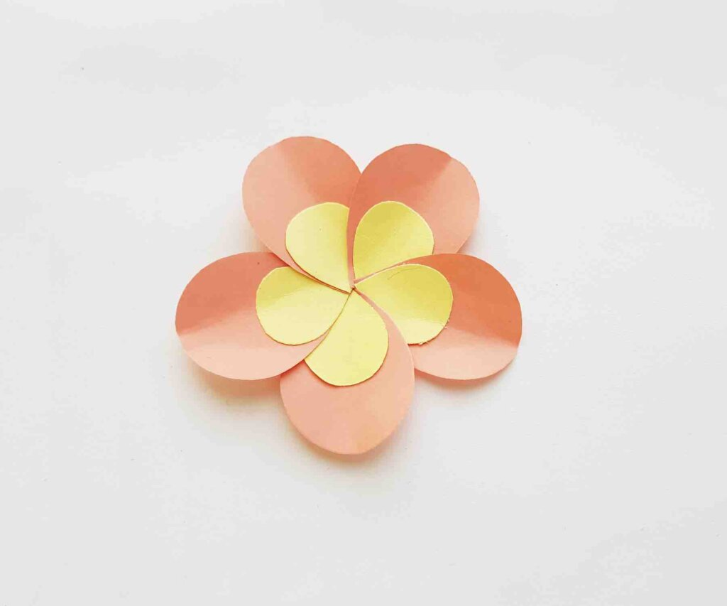 This is the last step for this paper flower tutorial by Hawaii Travel with Kids. Image of an orange and yellow paper plumeria flower.