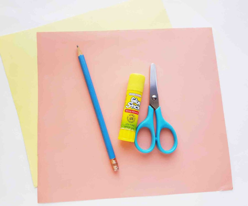 Learn how to make a paper flower by top Hawaii blog Hawaii Travel with Kids. Image of colored paper, a pencil, glue stick, and scissors.