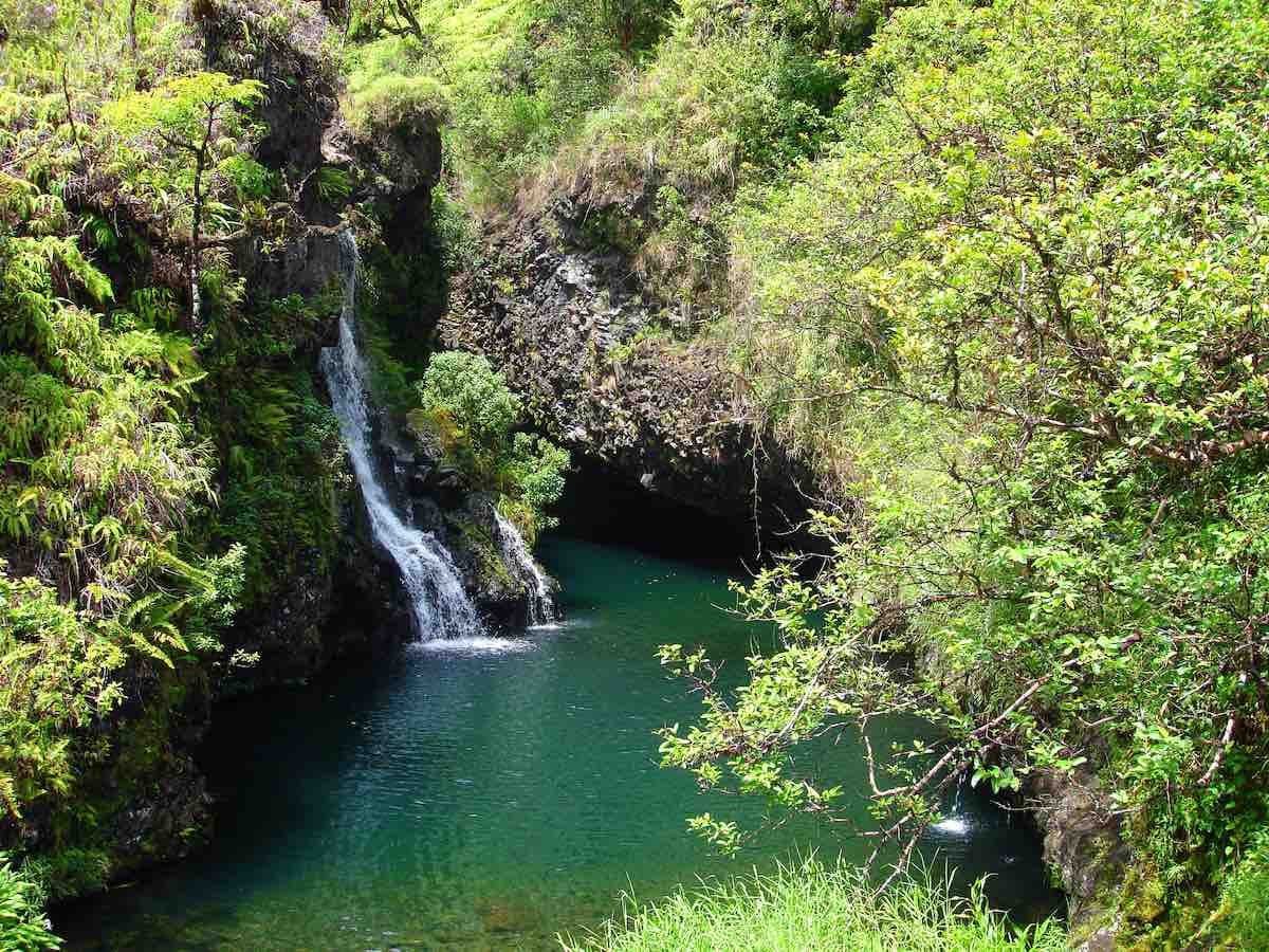 Find out the best Road to Hana stops for families by top Hawaii blog Hawaii Travel with Kids. Image of Waterfalls along the Road to Hana, Maui, Hawaii surrounded by lush greenery.