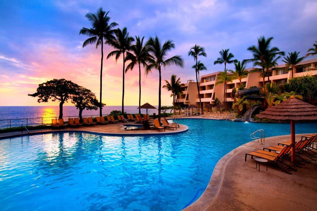 The Sheraton Kona Resort is one of the best hotels in Hawaii for families. Image of the pool area at sunset.