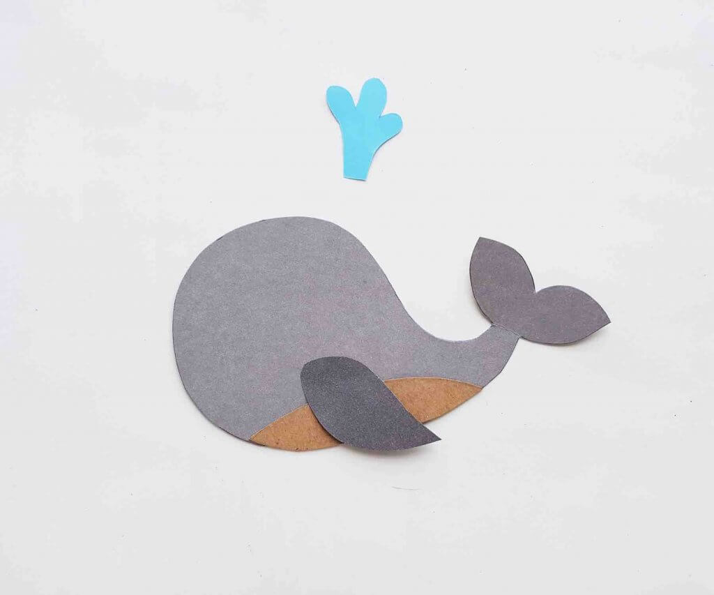 Start gluing the paper in this whale kids craft. Image of a paper whale partially assembled.