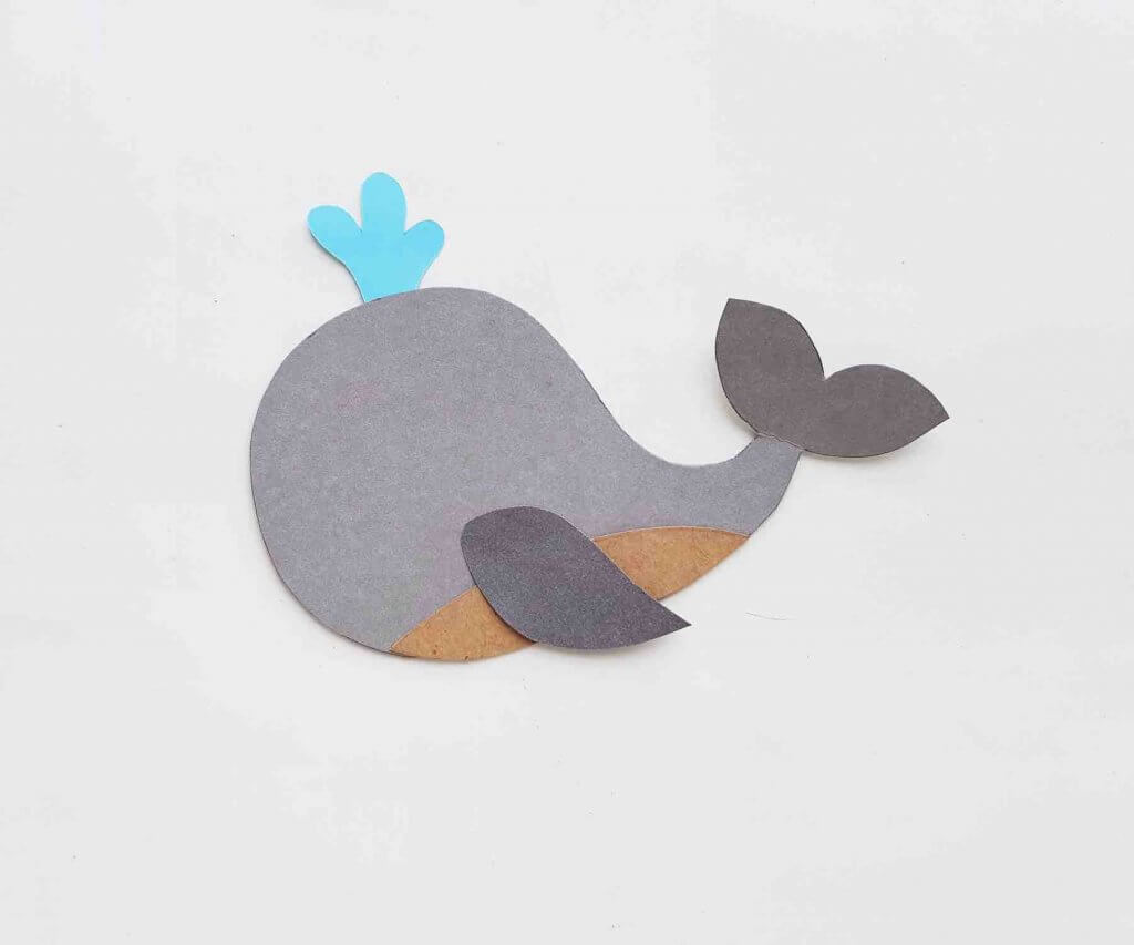 Attach the water spray to the top of this whale craft for kids. Image of a whale paper craft missing the face.