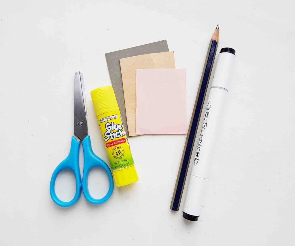 These are the craft supplies you'll need to make a whale out of paper. Image of scissors, glue stick, sharpie, pencil, and colorful papers.