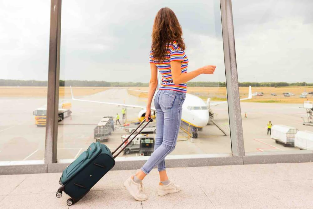 Find out what to add to your Hawaii packing list for the flight to Hawaii by top Hawaii blog Hawaii Travel with Kids. Image of a woman walking through the airport with a rolling suitcase.