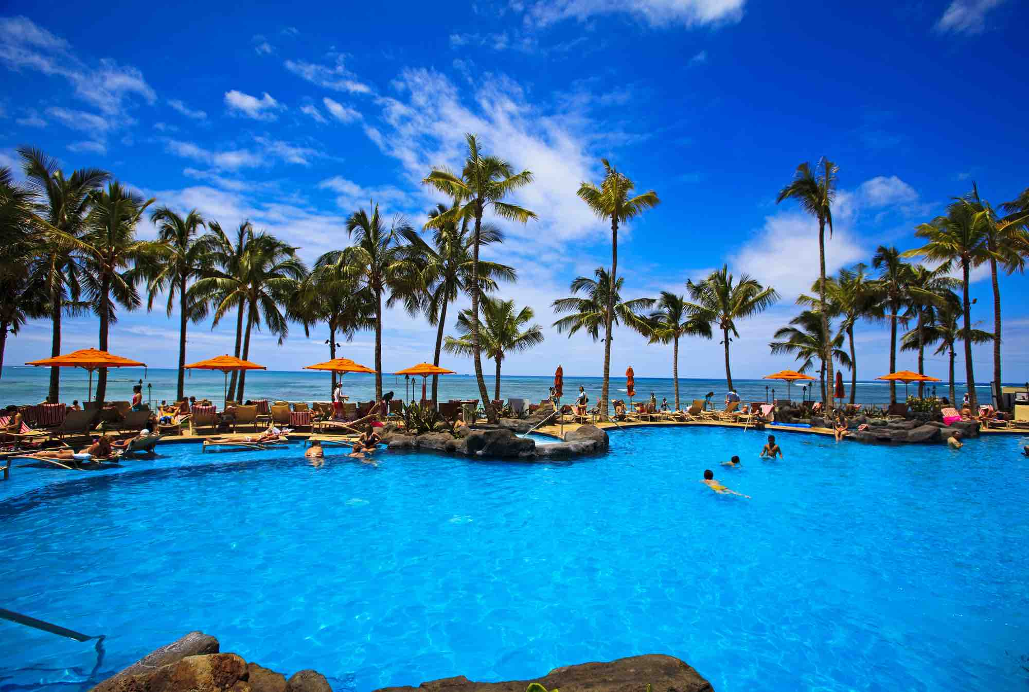 Find out the best resorts in Oahu for families recommended by top Hawaii blog Hawaii Travel with Kids. Image of a resort pool with palm trees and the ocean in the background.