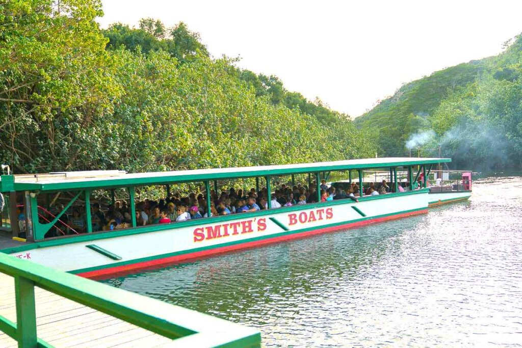 Take a Fern Grotto boat ride on this Wailua River tour before the Smith Family Luau. Image of a boat docked at the Wailua River.