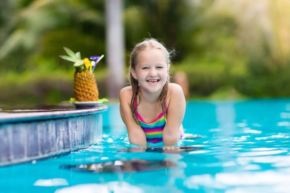 Find out the best Hawaii family resorts with kids club programming by top Hawaii blog Hawaii Travel with Kids. Image of a girl in a swimming pool with a pineapple drink.