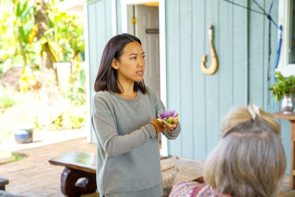 Image of a woman holding a Hawaiian plant at the Kauai Farmacy.