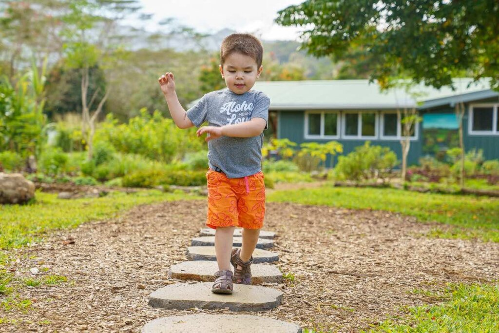 Image of a boy walking on stones on the North Shore Kauai Food Tour.