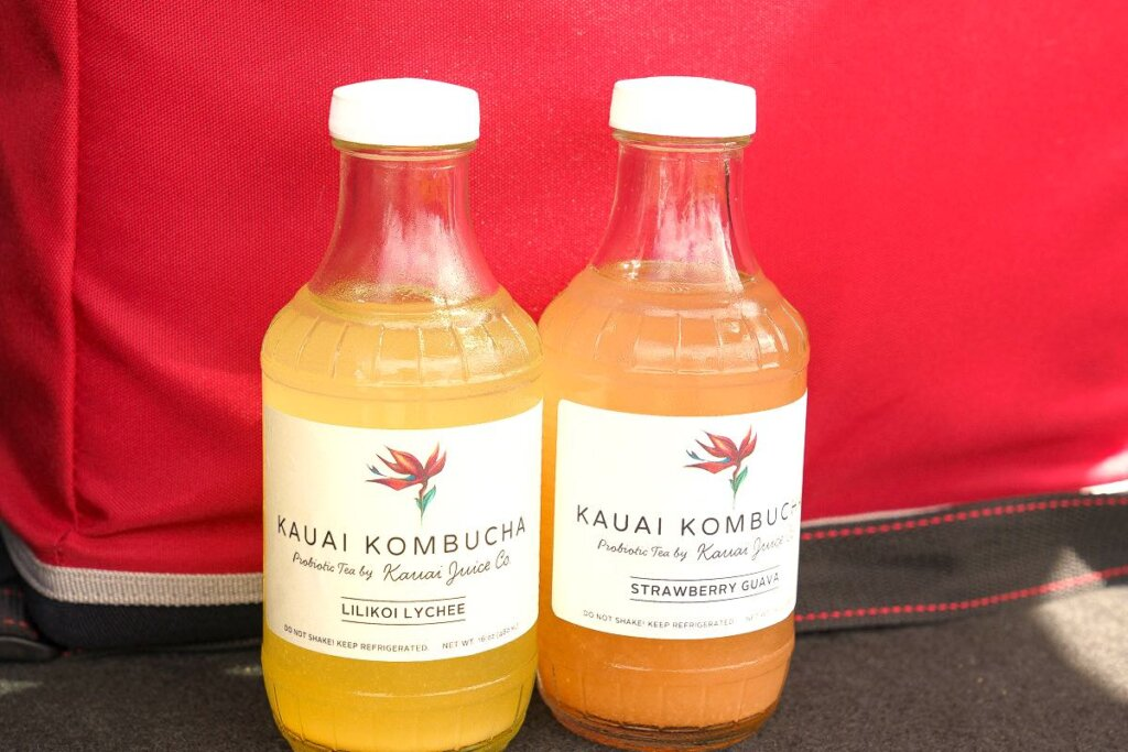 The first stop of the Tasting Kauai Food Tour is at Kauai Juice Co in Kilauea. Image of two bottles of Kauai Kombucha from Kauai Juice Co.