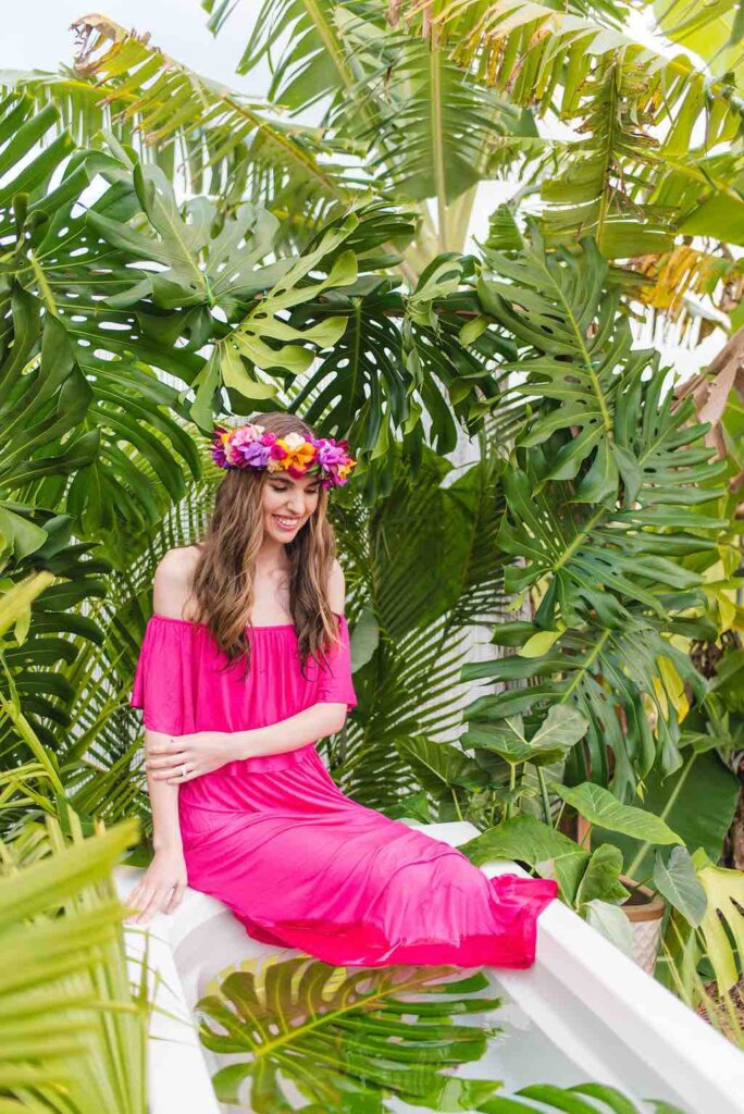 Bring lots of outfits for your photoshoot on Kauai. Image of a woman wearing a pink maxi dress as she sits at the edge of an outdoor bathtub on Kauai.