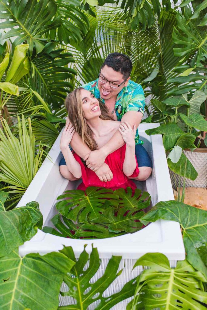 Image of a man and woman sitting in an outdoor Hawaiian bathtub fully clothed.