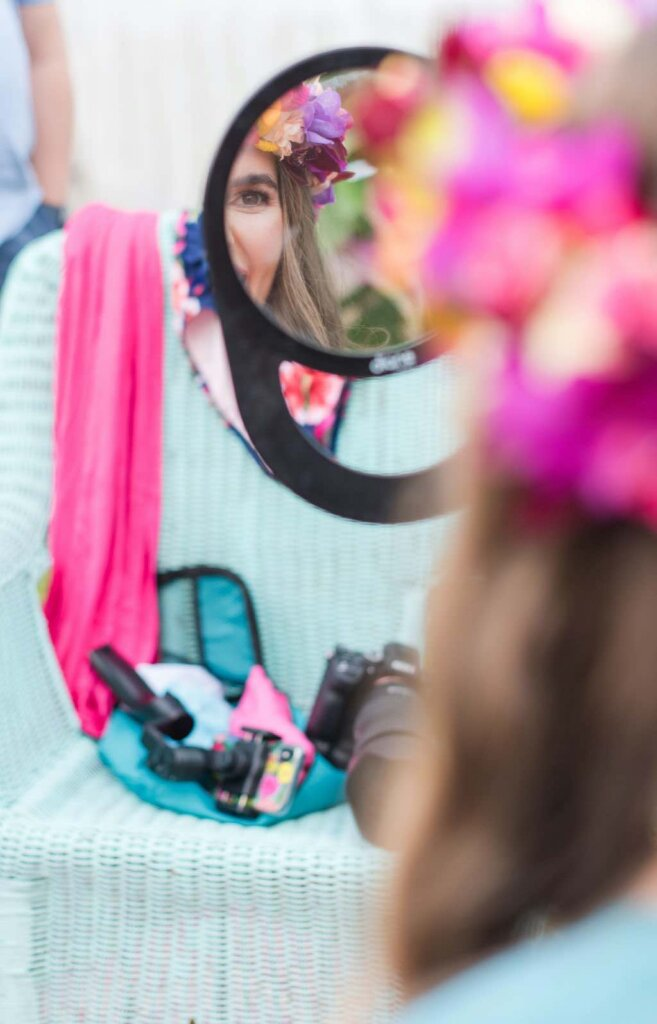 Image of a woman wearing a flower crown looking in a mirror before her photoshoot on Kauai.