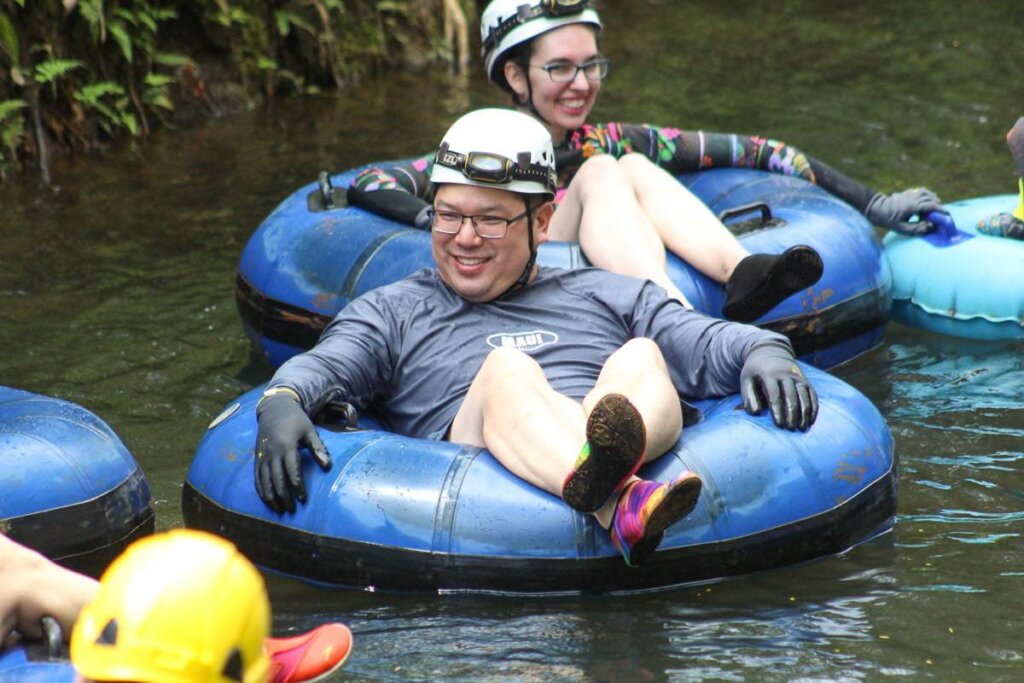 Find out what it's like to go mountain tubing on Kauai by top Hawaii blog Hawaii Travel with Kids. Image of a man and woman floating down a sugar cane canal on Kauai.