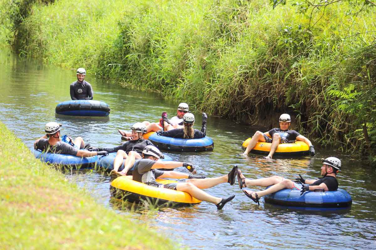 Find out why this Kauai tubing advenure is one of the best things to do in Kauai with kids by top Hawaii blog Hawaii Travel with Kids. Image of a group of people doing a Kauai river tube tour.