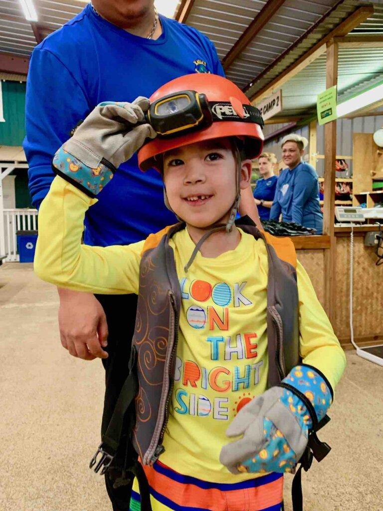 Image of a boy wearing a headlamp, rashguard, life vest, and gloves as he preps for a Kauai mountain tubing adventure.