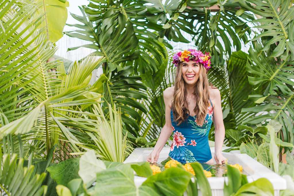 Bring along a cute swimsuit to your Kauai Jungle Tub photography session. Image of a woman wearing a floral swimsuit in an outdoor tropical bathtub.