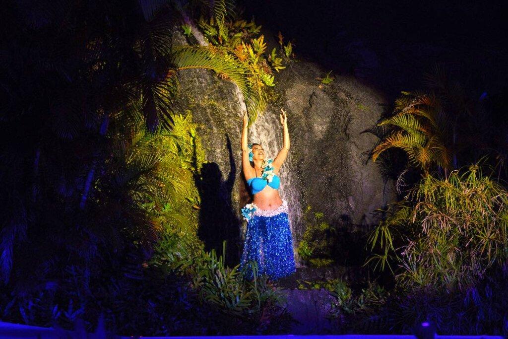 Image of a woman wearing a blue tinsel skirt while she dances hula on Kauai.