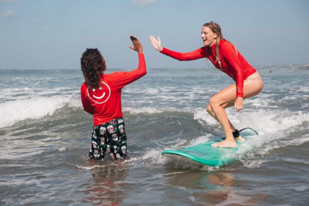 Always wear a rashguard when surfing on Oahu with kids. Image of a woman on a surfboard high fiving her instructor. Both are wearing red long sleeve rash guards.