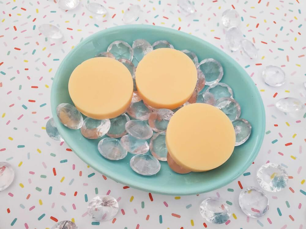 Learn how to make a DIY lotion bar with this Mango Butter Lotion Bar Recipe by top Hawaii blog Hawaii Travel with Kids. Image o a blue dish filled with 3 mango lotion bars.