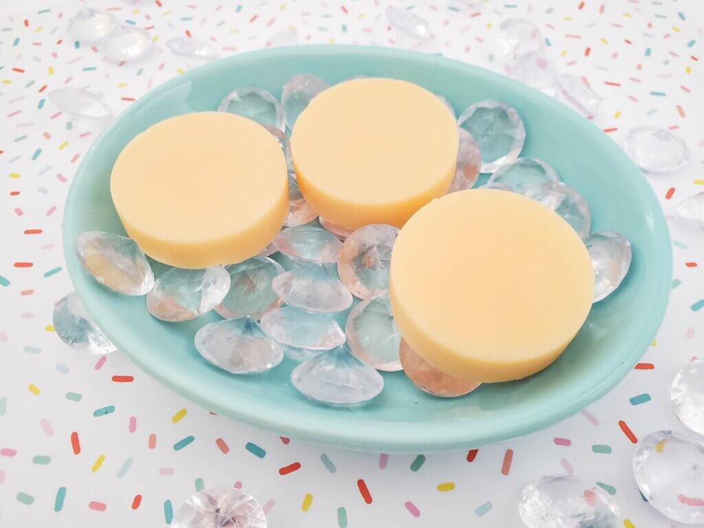 Now you know how to make mango lotion bars that smell like Hawaii! Image of 3 yellow mango lotion bars in a blue dish.