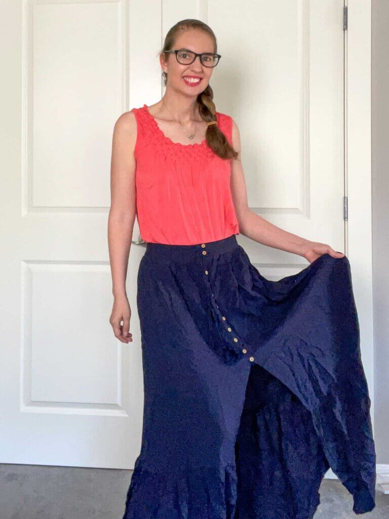 Image of a woman wearing a navy maxi skirt with a slit up the front.