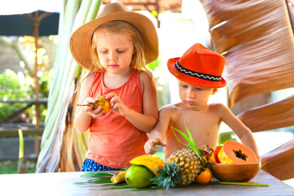 Find out the best Oahu babysitting services recommended by top Hawaii blog Hawaii Travel with Kids. Image of 2 kids tasting tropical fruit in Hawaii.
