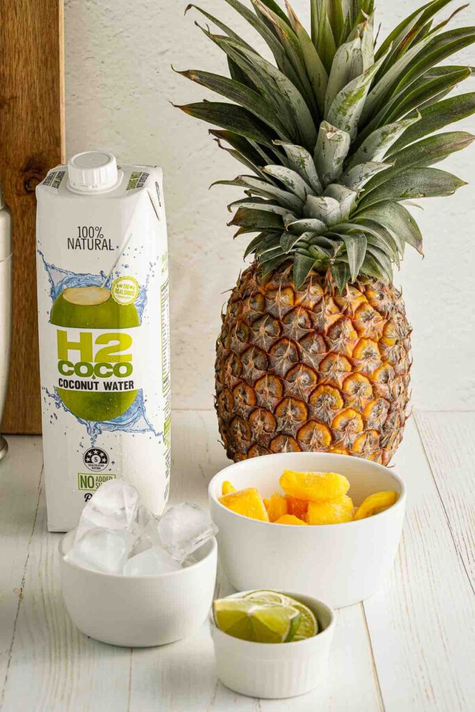 These are the pineapple mango mocktail recipe ingredients. Image of a pineapple, coconut water, frozen mango, lime, and ice.