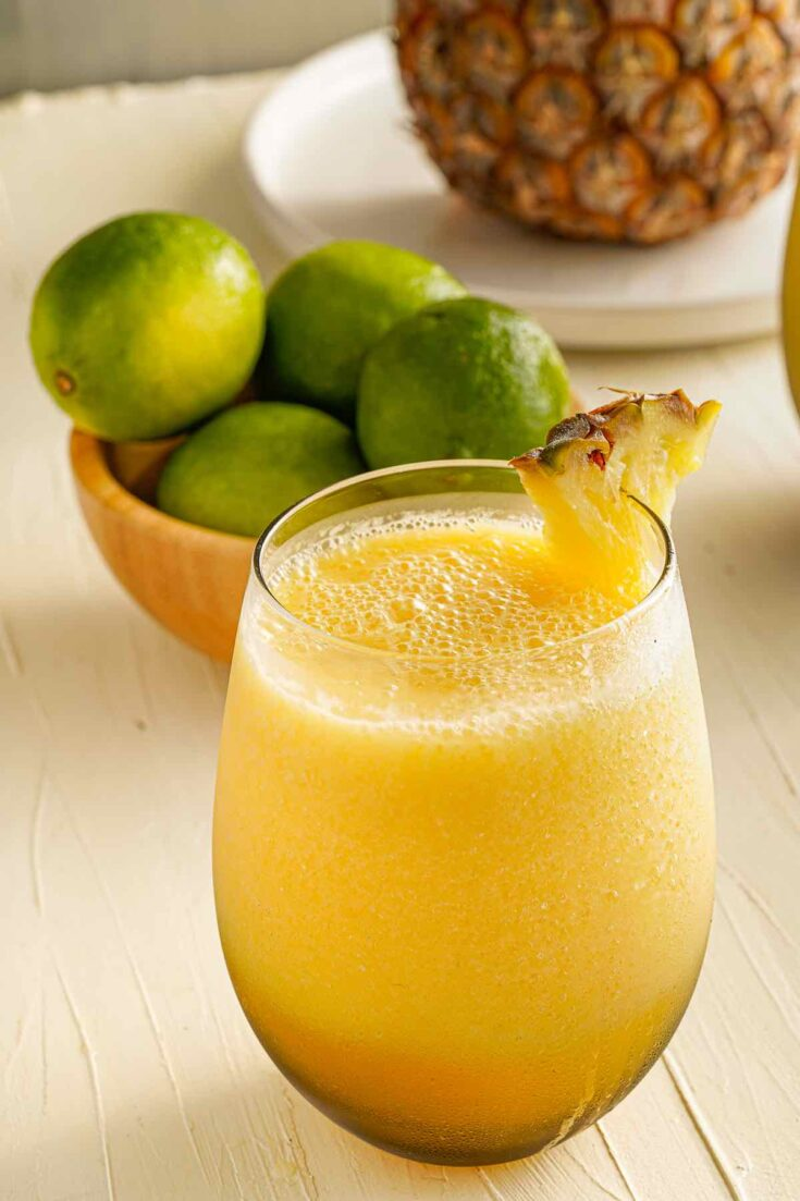 Find out how to make this frozen pineapple mango mocktail by top Hawaii blog Hawaii Travel with Kids. Image of a tropical drink with a pineapple garnish.