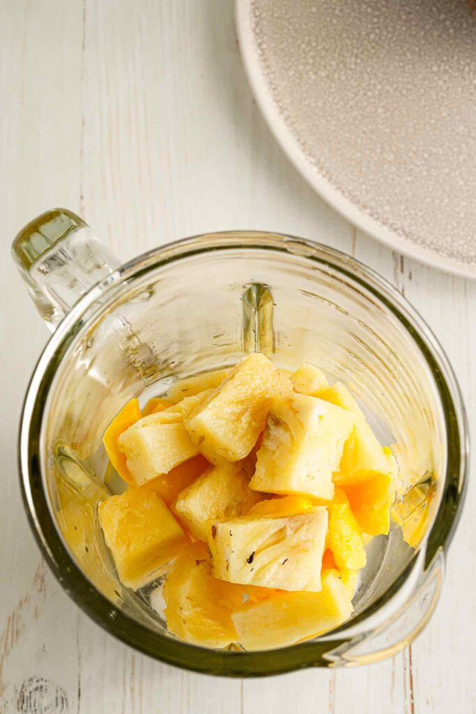 Place all the mango pineapple mocktail ingredients in a blender. Image of frozen mango, pineapple, coconut water, lime, and ice in a blender.