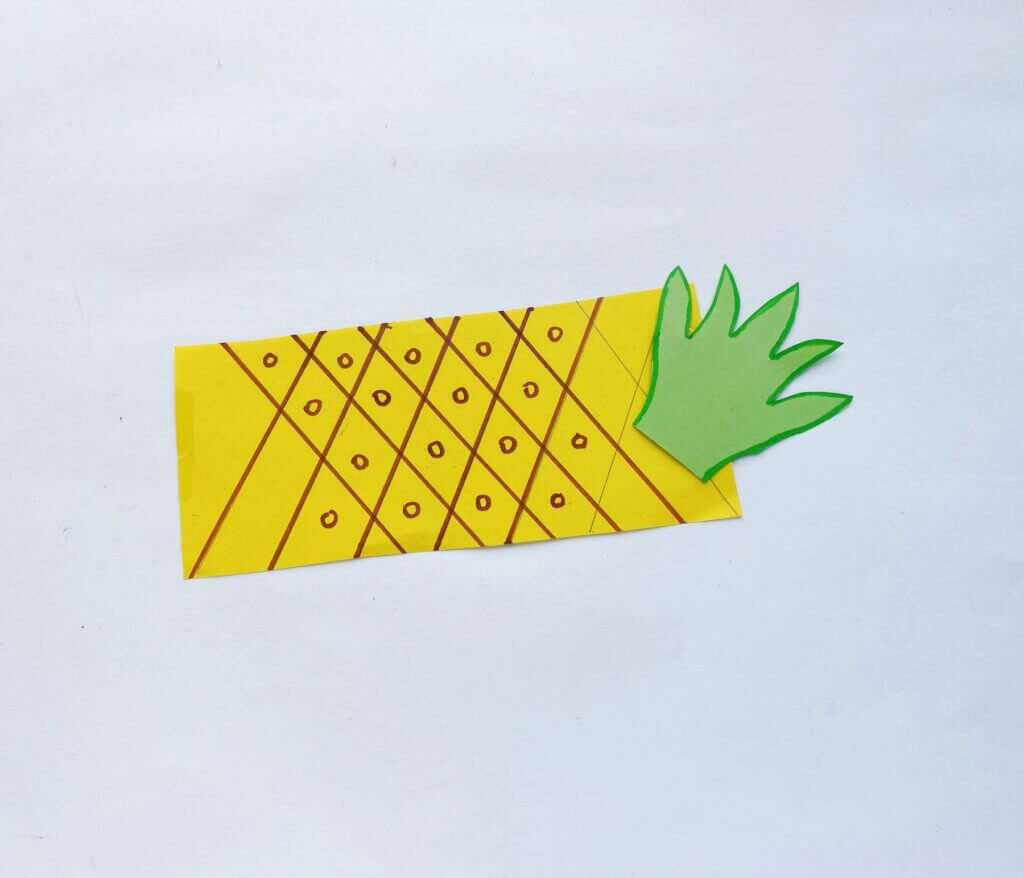 Use a ruler to draw lines on your pineapple when creating this pineapple craft for toddlers. Image of a yellow strip of paper with criss cross brown lines and circles on it.