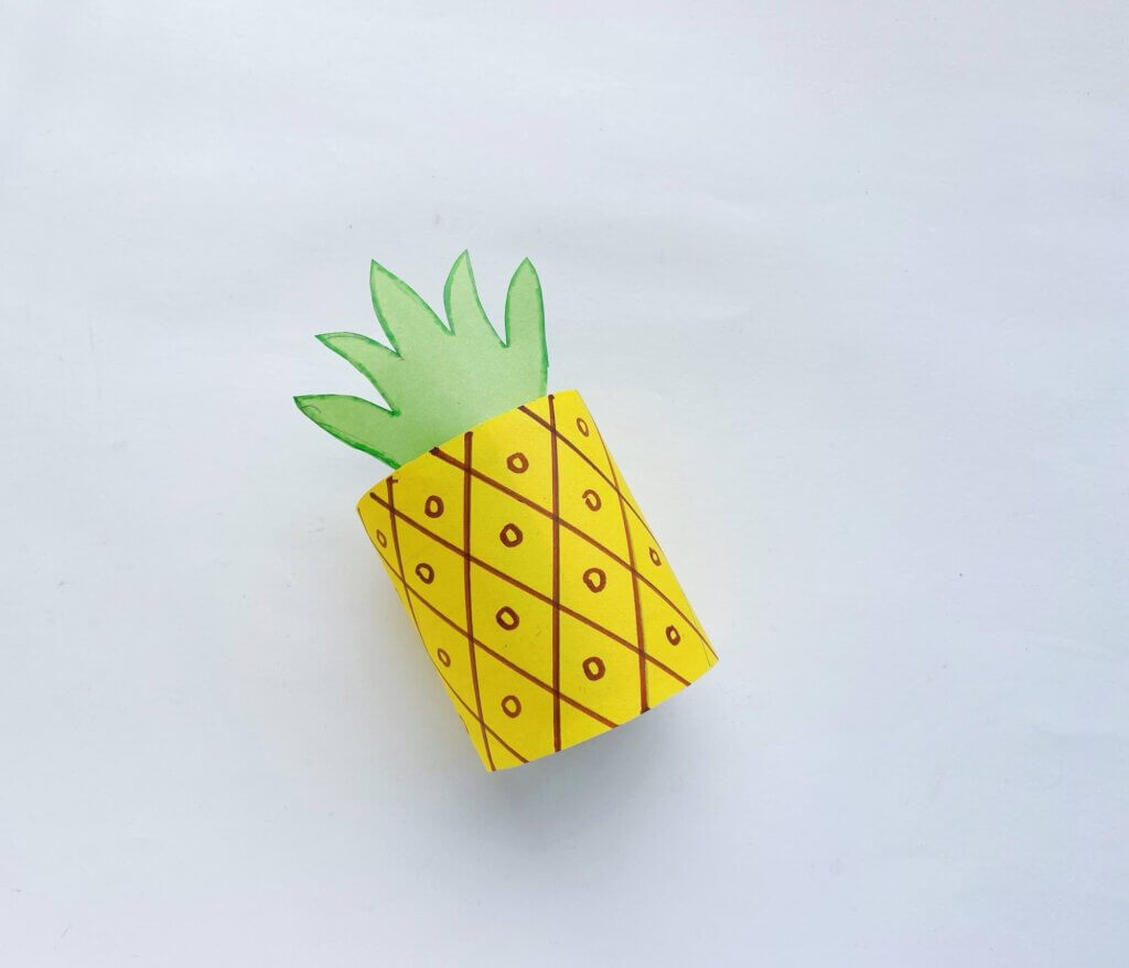 Glue the leaves to the top of the toilet paper roll and that's it! Image of a toilet paper roll pineapple craft for kids.