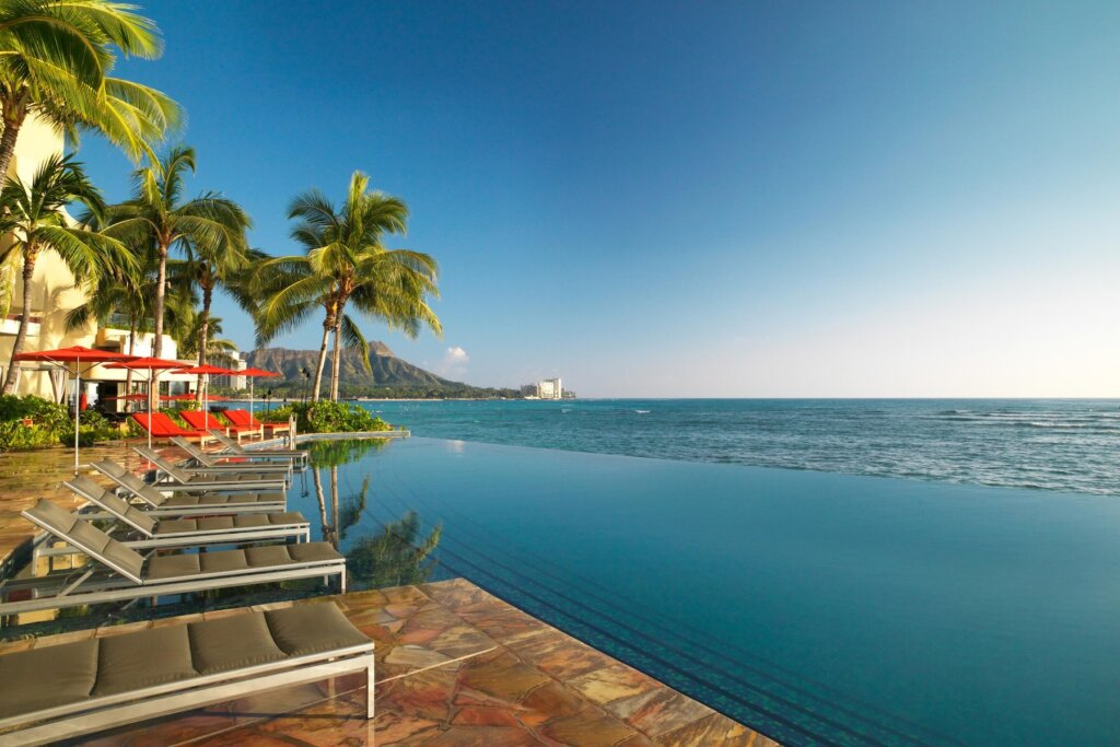 The Sheraton Waikiki is one of the Best Resorts in Oahu for Families wanting to stay in Waikiki. Image of some lounge chairs at the infinity pool at Waikiki Beach.