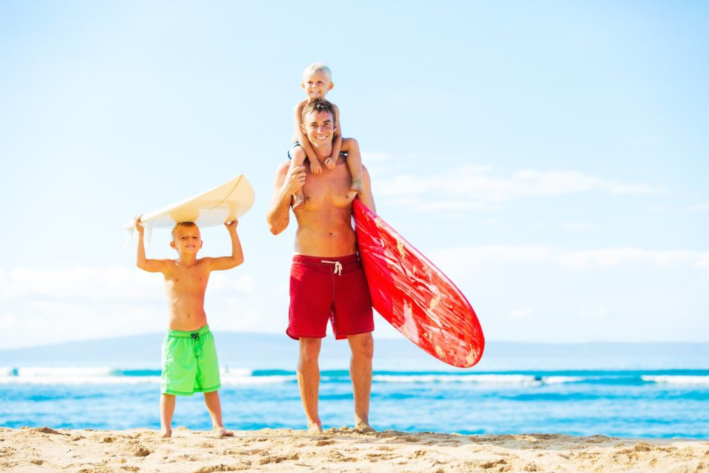 Find out where to book Kauai surfing lessons for kids recommended by top Hawaii blog Hawaii Travel with Kids. Image of a father and young sons going surfing at the beach.