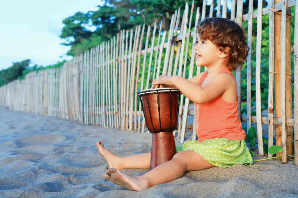 Find out the best babysitters in Maui recommended by top Hawaii blog Hawaii Travel with Kids. Image of a little girl playing a drum on a beach.