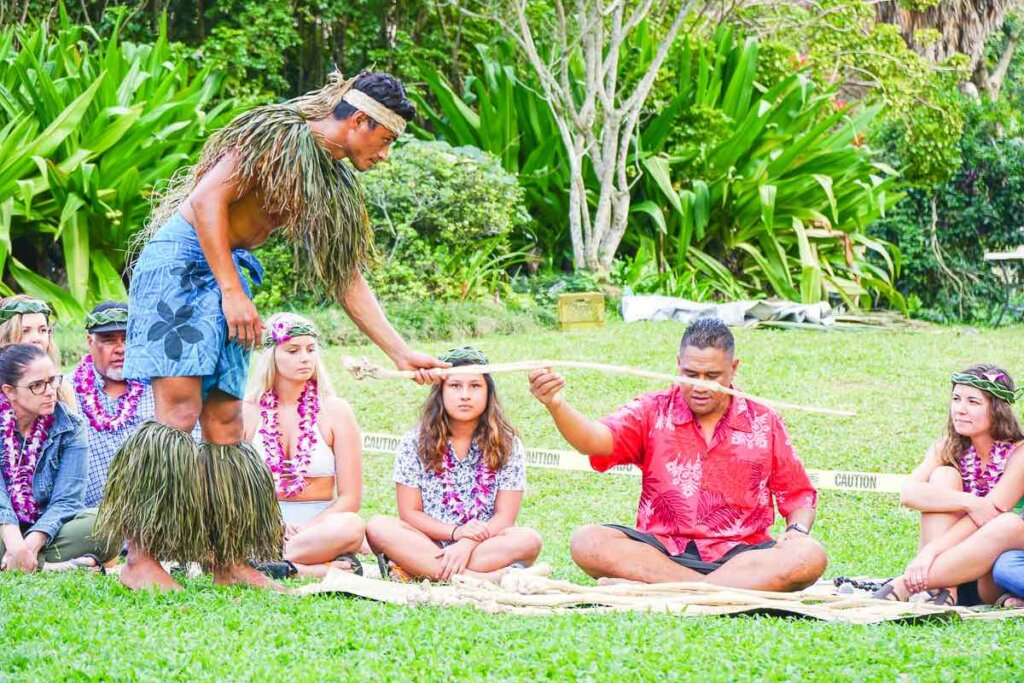 This Samoan kava ceremony is one of the reasons why Toa Luau is one of the best luaus in Oahu Hawaii. Image of a man handing a stick to a Samoan chief who is sitting on the grass.