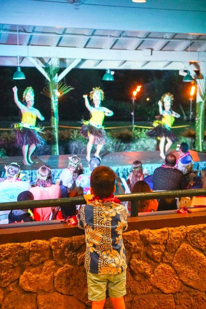 Image of a boy watching a North Shore luau on Oahu.