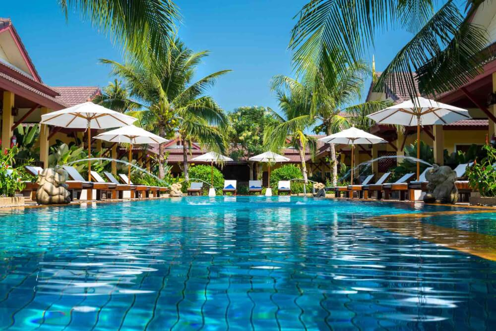 Wondering where do celebrities stay in Hawaii? Find out 6 Hawaii luxury hotels that attract the rich and famous by top Hawaii blog Hawaii Travel with Kids. Image of a tropical resort pool.