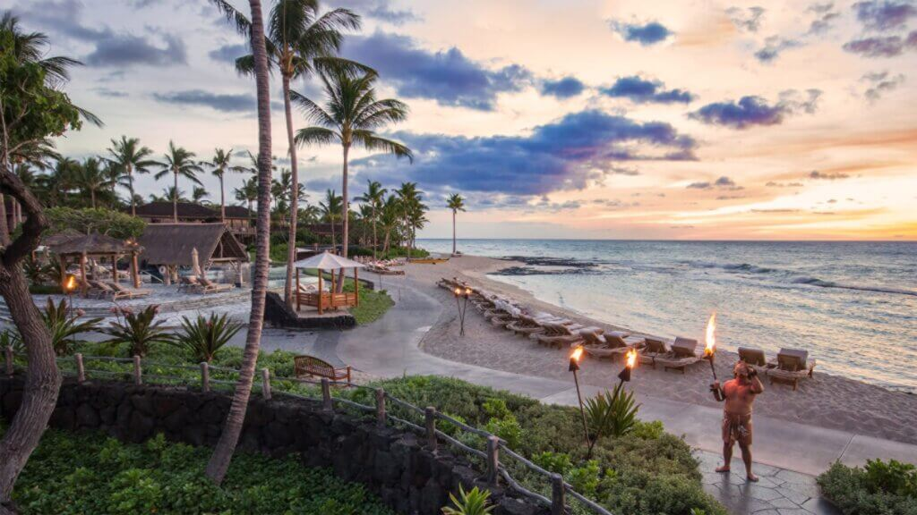 The Four Seasons Resort Hualalai tops our list of where to stay in Big Island with kids. Image of a torch lighting ceremony on the beach in Hawaii.