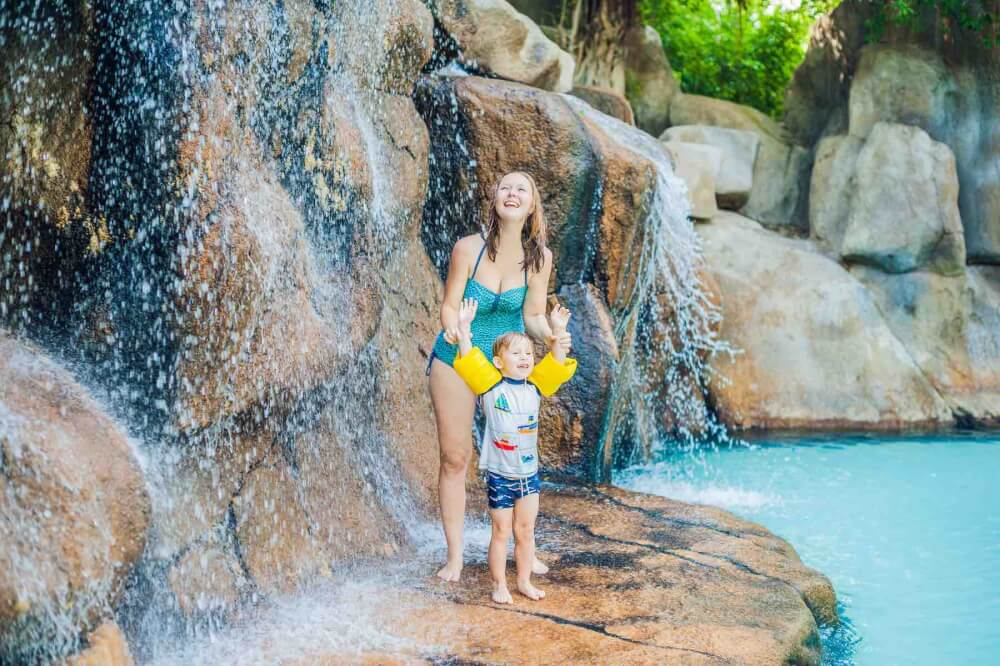 Find out the best resorts in Kauai for families recommeded by top Hawaii blog Hawaii Travel with Kids. Image of a mother and sun having fun at a waterfall at a Hawaii resort pool.