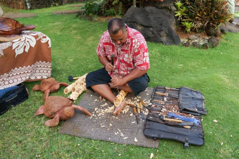You'll have the opportunity to see Hawaiian artisans like this one carving wood sculptures.