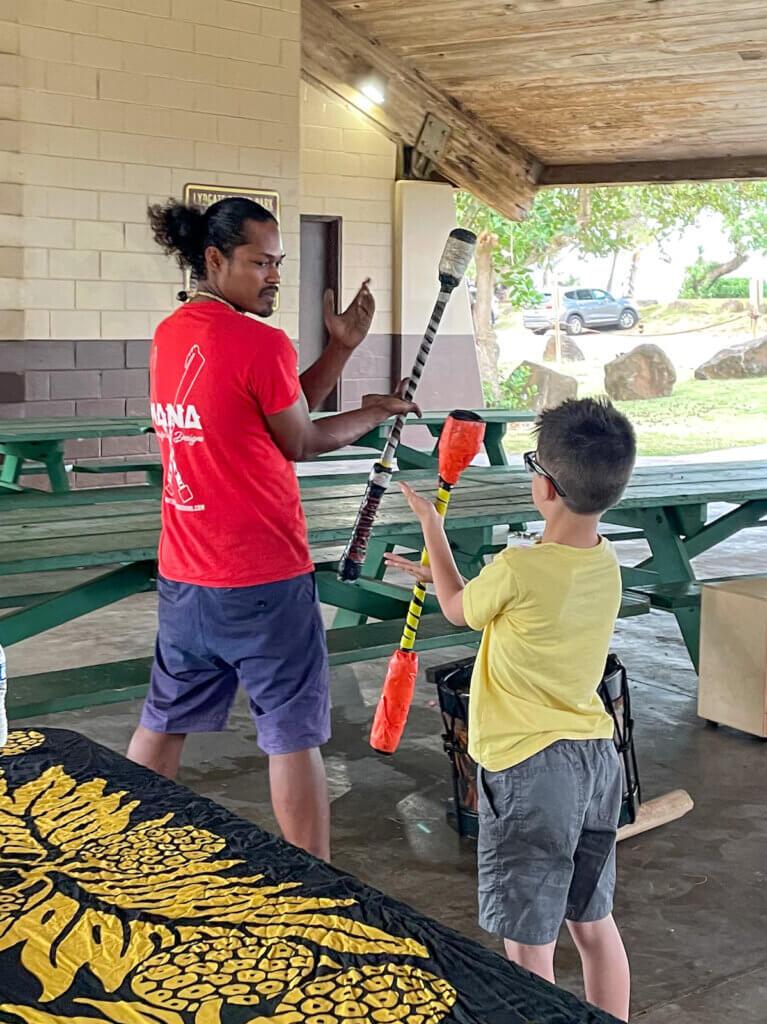 Image of a man teaching a boy how to do Hawaiian fire knife dancing.